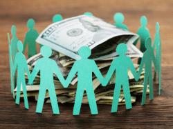 paper dolls around pile of dollar bills